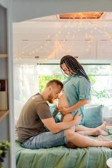 夫はトレーラーで妊娠中の妻にキスします