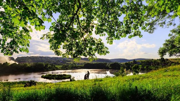 湖の近くの美しい空と自然を背景に、夫は妊娠中の妻の腹にキスをする