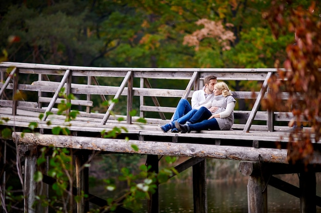 Husband kisses his pregnant wife sitting on a wooden bridge