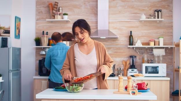 남편이 부엌에서 도마에 피망을 자르고 있는 동안 아내 뺨에 키스합니다. 건강한 유기농 식품을 준비하는 요리는 행복한 함께 생활합니다. 야채와 함께 가족의 즐거운 식사