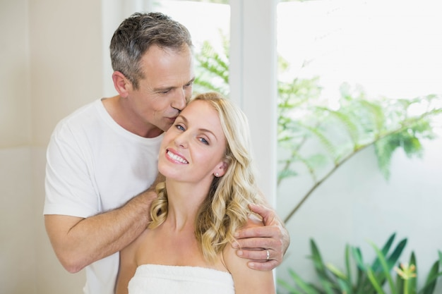 Husband kissing wife on the forehead in the living room