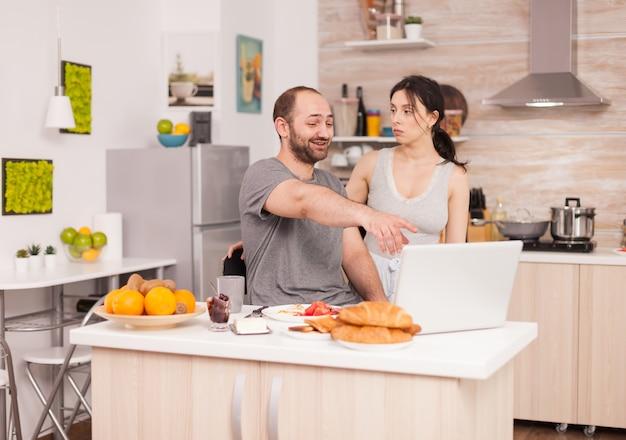 남편이 노트북에 있는 사진을 보여주는 아내를 보고 웃고 있습니다. 말다툼, 갈등, 절박한 문제 말다툼과 결혼 생활 갈등, 슬픈 감정과 절망적이고 불행한 부부