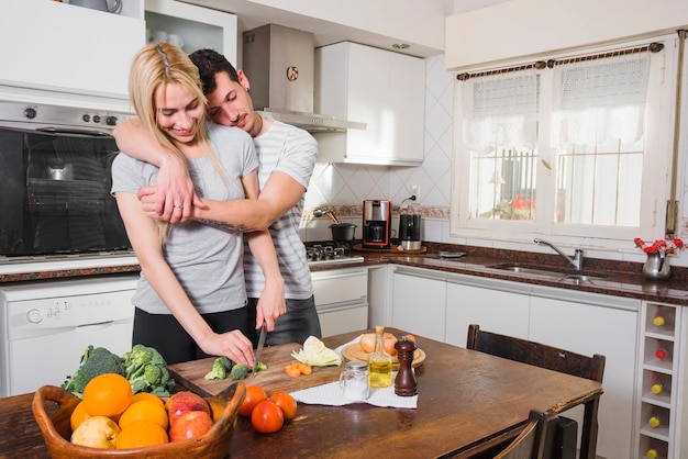 Husband leaning on his wife's shoulder cutting vegetables with knife
