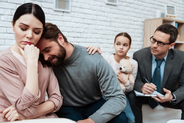 Husband lie on woman shoulder psychologist office