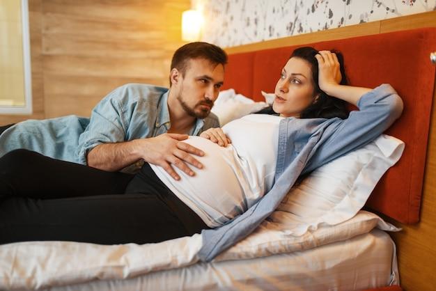 夫は自宅で妊娠中の妻のお腹の中で赤ちゃんの声に耳を傾けます。妊娠、出生前の期間。妊娠中のママとパパがソファで休んでいる、ヘルスケア
