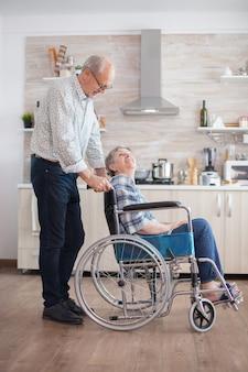 남편이 부엌에서 장애인 노인 여성을 바라보고 있습니다. 창을 통해 찾고 부엌에서 휠체어에 앉아 장애인된 수석 여자. 장애인과 함께 살기. disabi와 아내를 돕는 남편