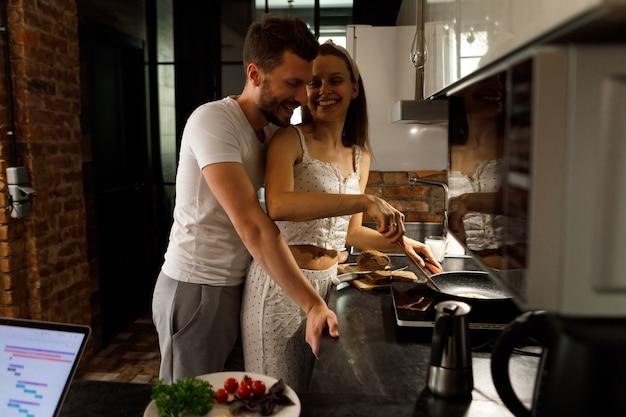 夫は彼の妻が準備しているものを見ます。カップルは笑っています。