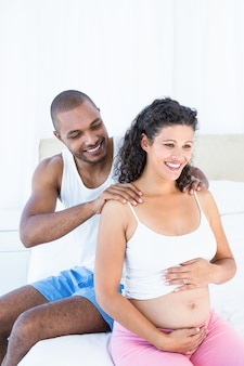 Husband massaging pregnant wife shoulders