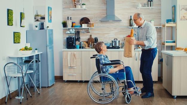 남편은 슈퍼마켓에서 집에 도착한 후 식료품 종이 봉지를 들고 휠체어를 탄 노인 여성을 밀었습니다. 아침 식사를 위해 신선한 야채를 곁들인 성숙한 사람들.