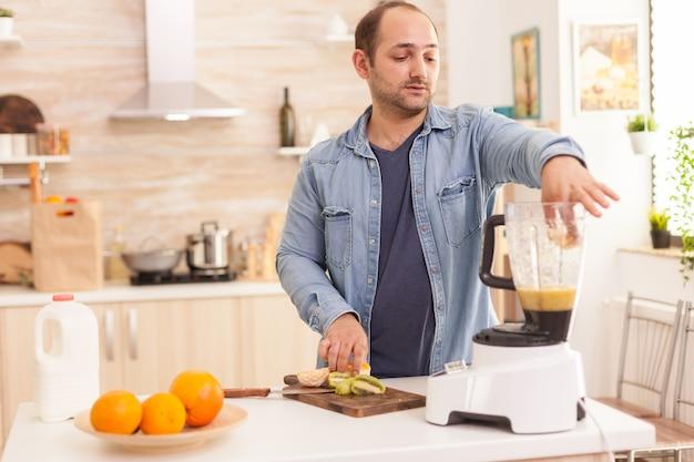 Marito che mette i frutti nel frullatore per mescolarli per un frullato sano. stile di vita sano e spensierato, mangiare dieta e preparare la colazione in un'accogliente mattinata di sole