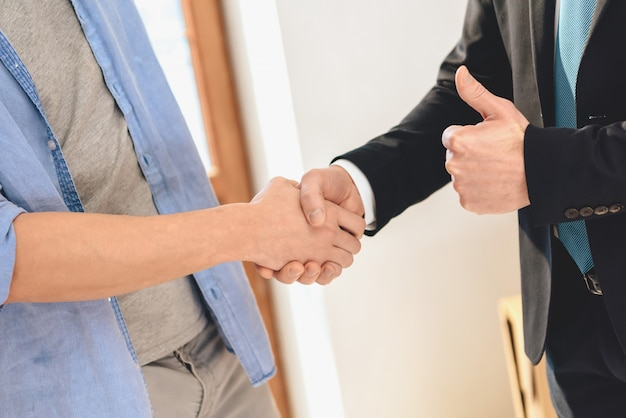 Husband and realtor in suit are shaking hands.