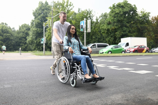 Husband rolls a wheelchair with a young wife