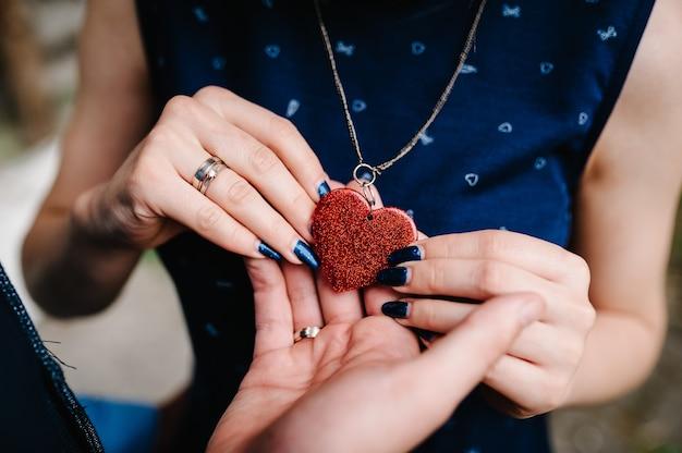 Руки мужа и женщины держат ожерелье в форме сердца, висящее на его шее