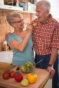 Marito che assaggia un'insalata di verdure fatta in casa