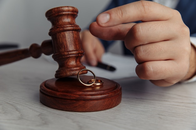 Husband signing divorce contract mans hand gavel of judge and rings