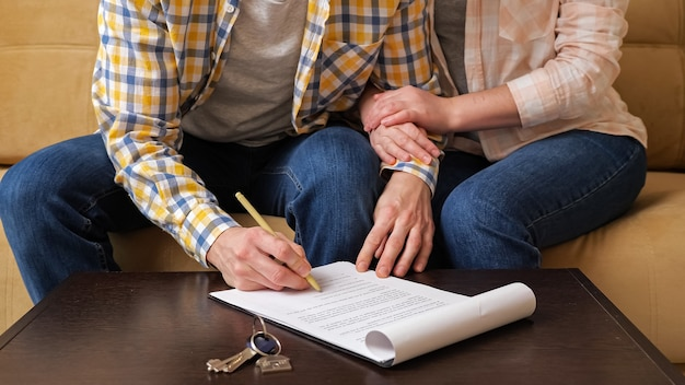Husband signs apartment purchase contract near wife on sofa