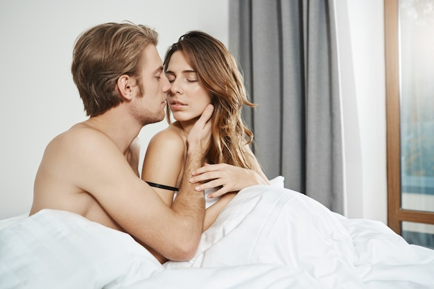Husband sitting in bed with wife, holding hand on her face and kissing while her eyes closed and hand gently touched his arm start of sensual morning foreplay of newly wedds.
