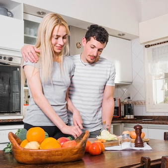 Husband standing with her wife cutting vegetables on table