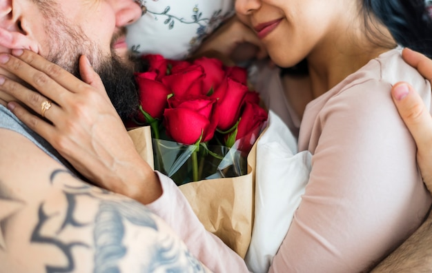 Husband surprised wife with red rose bouquet