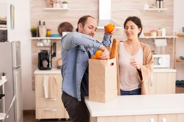 아내와 함께 부엌에 있는 식료품 가방에서 오렌지를 꺼내는 남편. 남성과 여성을 위한 건강한 행복한 관계 생활 방식, 함께 쇼핑 제품