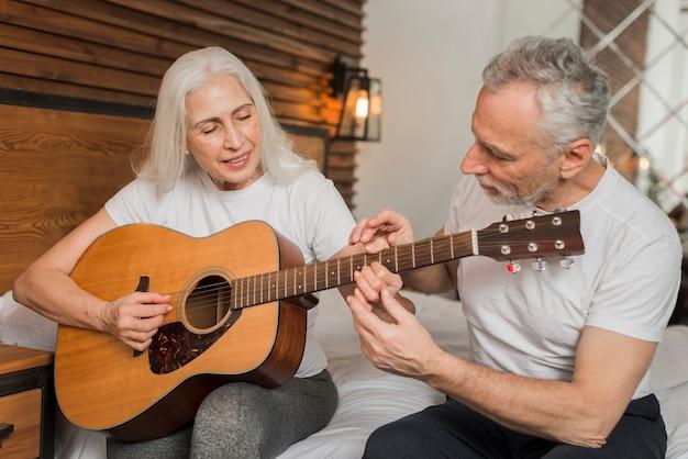 Husband teaching wife to play quitar
