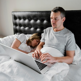 Husband using laptop while wife is asleep