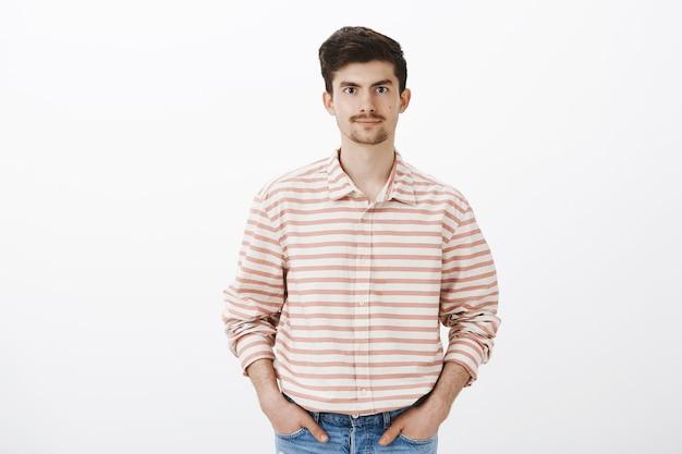 夫が妻に買い物リストを与えるのを待っています。口ひげとあごひげをストライプのシャツにした成熟した普通のヨーロッパ人、ポケットに手をつないで丁寧に笑顔、リラックスしてカジュアル