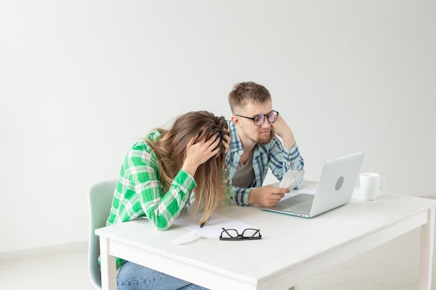 Husband and wife discuss amount in check for payment of the apartment and compare it with the rates on official website while sitting at the table with laptop. concept of payment of utility bills.