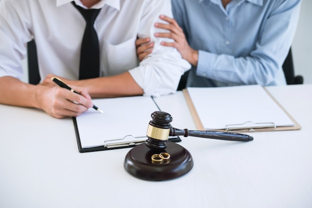 Husband and wife during divorce process with lawyer or counselor and signing of divorce