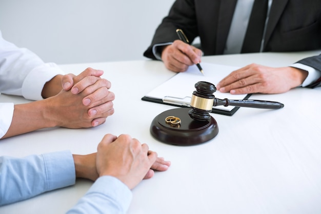 Husband and wife during divorce process with lawyer and signing of divorce contract