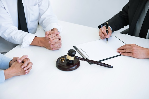 Husband and wife during divorce process with male counselor and signing of divorce