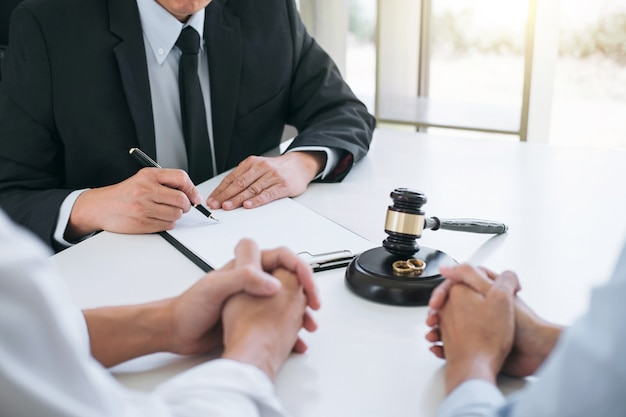 Husband and wife during divorce process with male counselor and signing