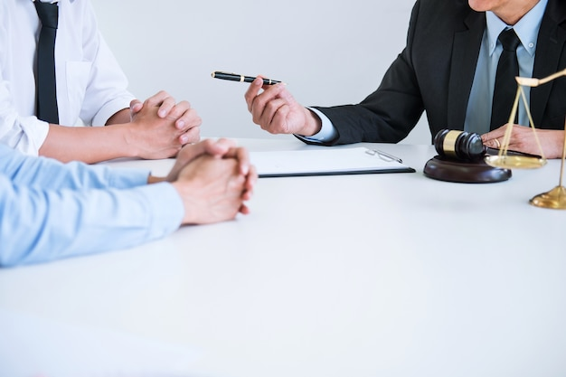 Husband and wife during divorce process with senior male lawyer or counselor
