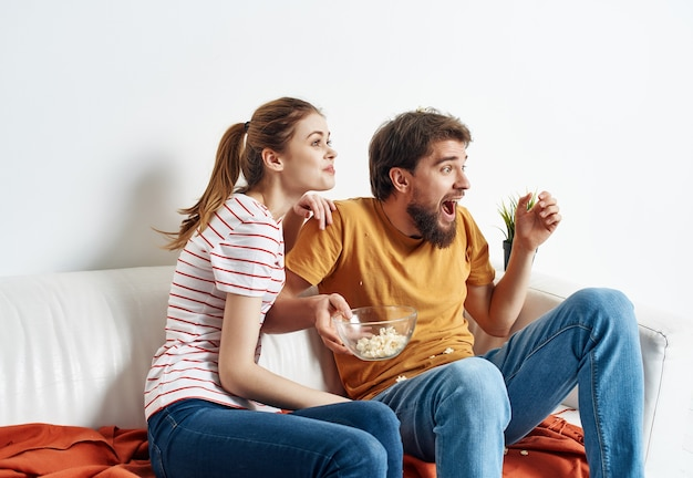 Husband and wife have fun at home on the couch popcorn watching movies