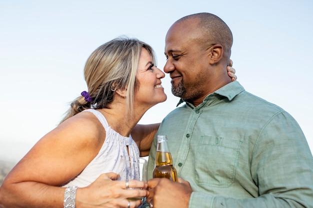 Marito e moglie che bevono un drink sul balcone