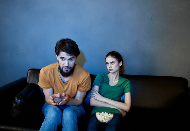 Husband and wife at home in the evening on the couch watching tv rest popcorn