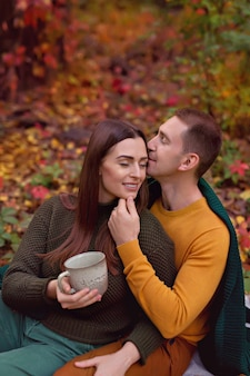 Husband and wife hug each other for an autumn picnic with pumpkin, apples, tea