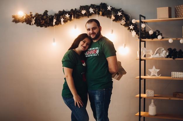 Husband and wife hugging, posing in studio.
