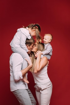 Husband and wife kissing with children on shoulders.