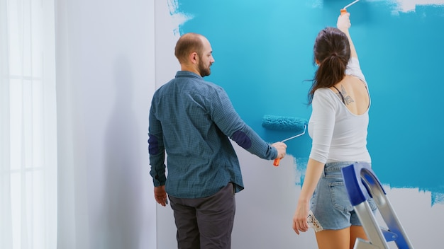 Husband and wife painting apartment wall with blue paint using roller brush. apartment redecoration and home construction while renovating and improving. repair and decorating.