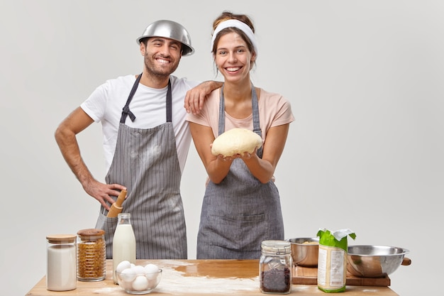 Husband and wife pose in the kitchen preparing tasty dinner