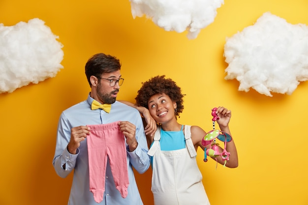 Husband and wife pose with baby items prepare for becoming parents. cheerful pregnant woman holds mobile toy looks gladfully at man isolated over yellow background. parenthood pregnancy concept