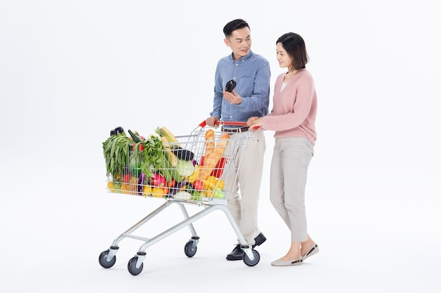 Husband and wife shopping for vegetables at the supermarket