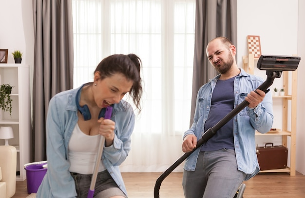 Husband and wife singing together while cleaning apartment