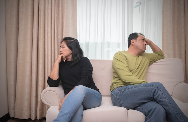 Husband and wife sitting on different sides of sofa. quarrel concept