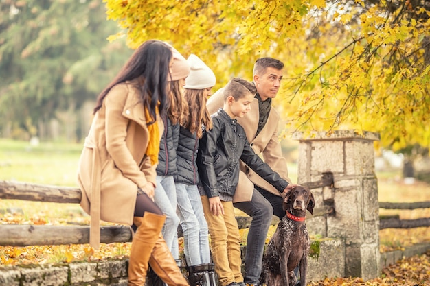 남편, 아내, 세 아이, 개가 야외 난간에 앉아 가을날을 즐기고 있습니다.