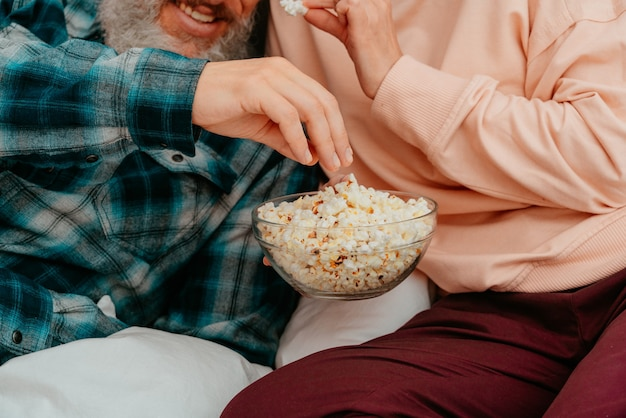 Husband and wife watch a film on the bed and eat popcorn