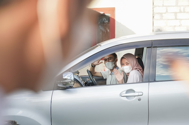 A husband and wife wearing masks wave their hands from inside the car