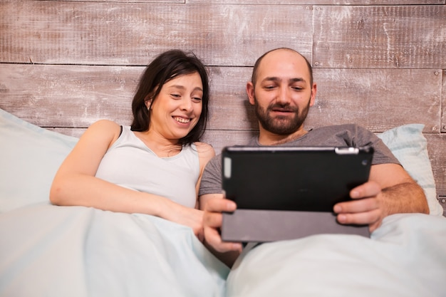 Husband and wife wearing pajamas laughing while watching a funny video on tablet computer.