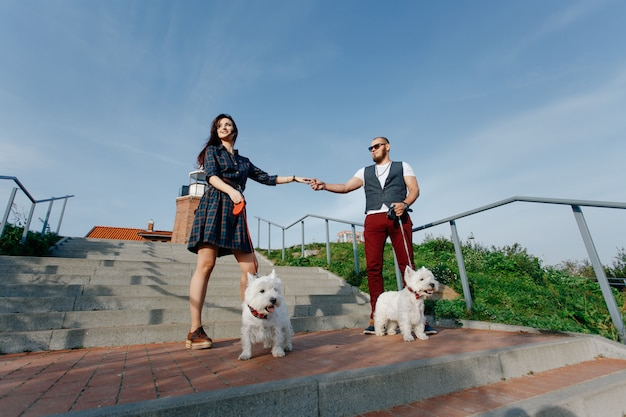 Муж с красивой женой выгуливают своих белых собак на улице
